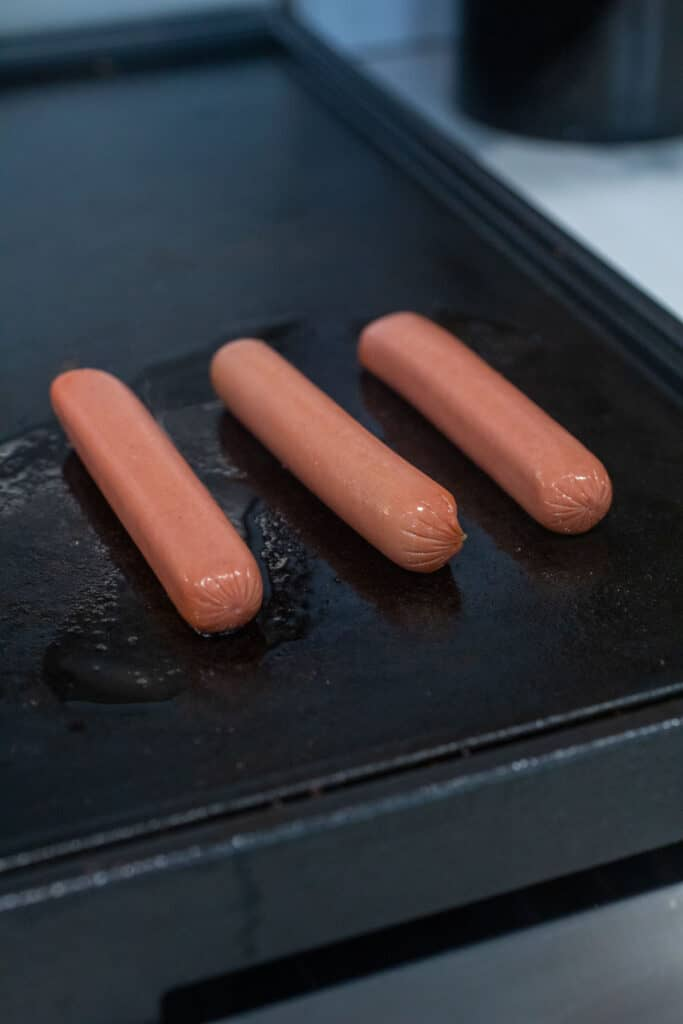 Cooking the hot dogs on a griddle or pan.