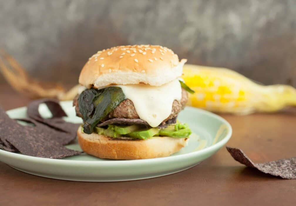 Santa Fe Burgers: One of my favorite burgers to toss on the grill in the summer. Topped with a spicy cheese sauce, roasted poblano peppers, and crispy blue corn chips! | macheesmo.com