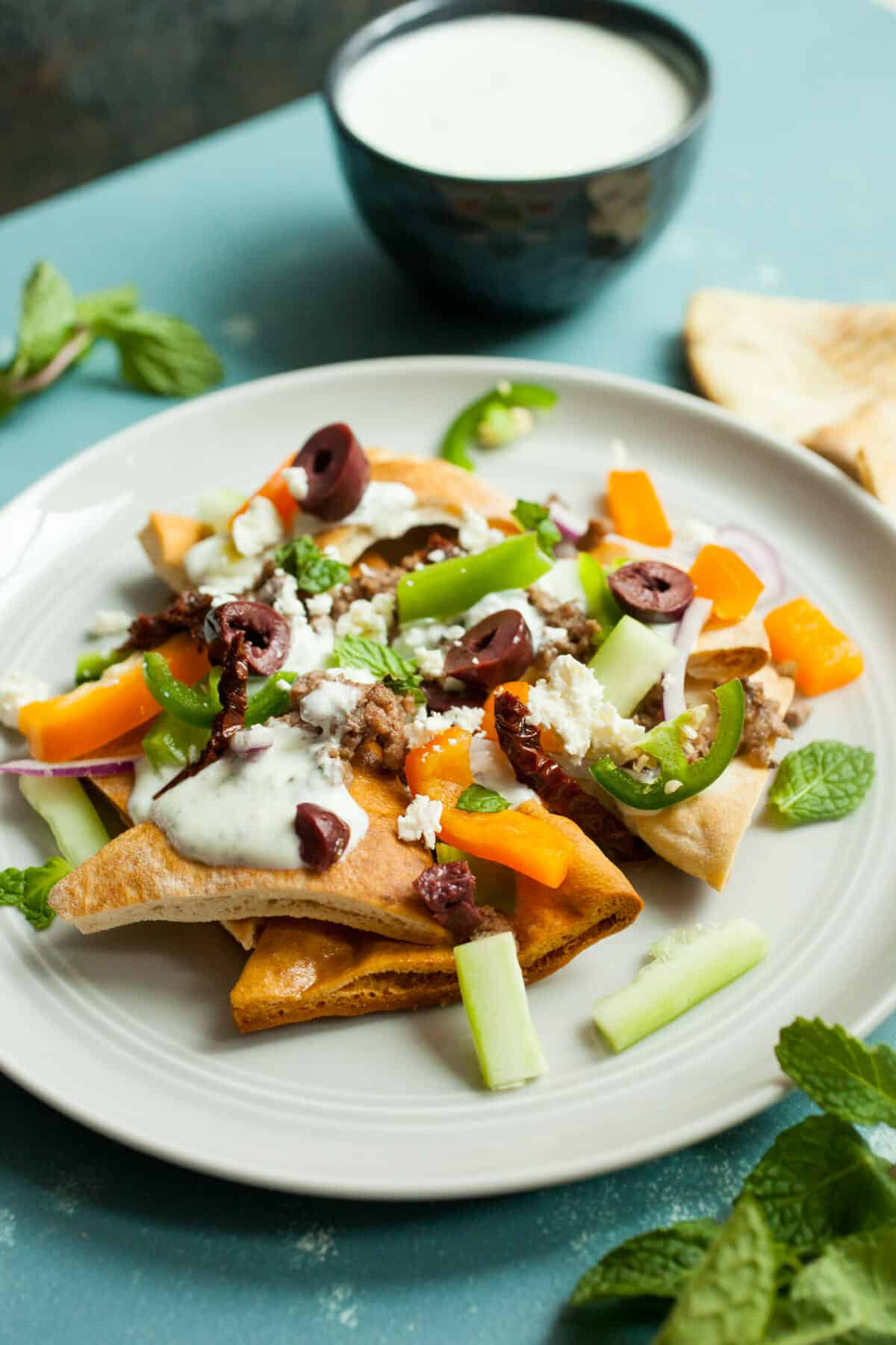 Greek Nachos: Toasted crispy pita chips topped with lamb, a simply feta sauce, and loads of Mediterranean veggies. One of the few nachos that are actually fine a bit cold or room temperature! So delicious and fresh! | macheesmo.com