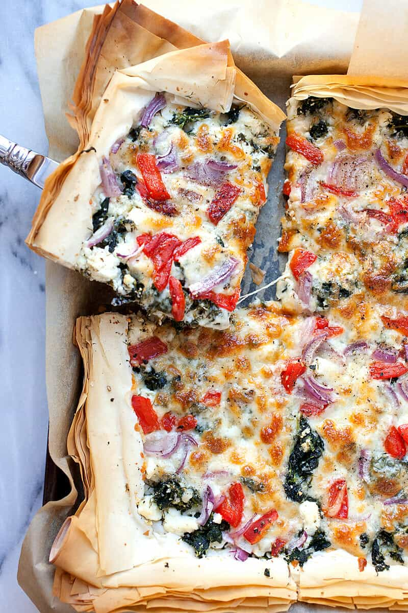 Spanakopizza: A perfect mash-up between flaky spanakopita and a delicious pizza. Loaded with spinach, feta, and roasted red peppers, but it still has a flaky phyllo dough crust! Great for a meal or appetizer. | macheesmo.com
