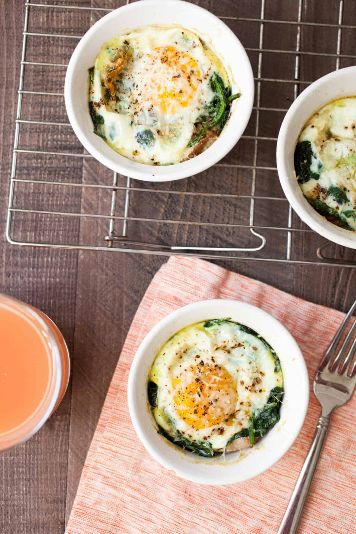 Bacon Spinach Baked Eggs: These individual baked eggs are perfect for breakfast or a group brunch. Just a few ingredients and everything you want in a breakfast (toast, bacon, veg, and egg) all in one dish! | macheesmo.com