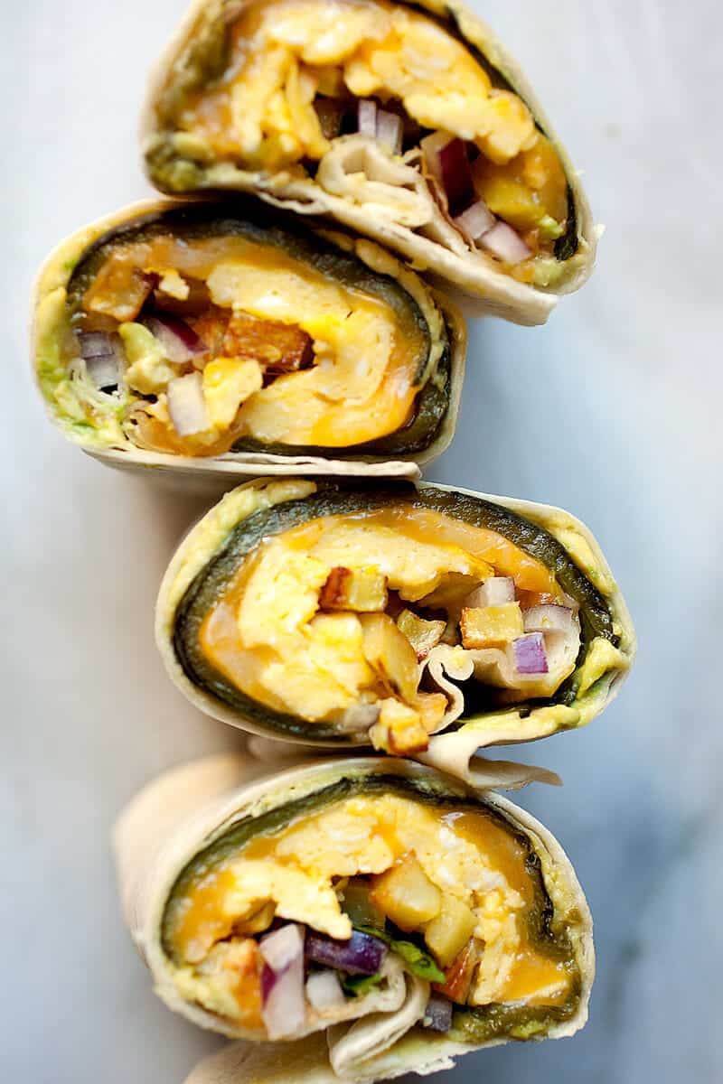 Chile Relleno Burritos: Stuffed poblano peppers rolled right inside a big tortilla with a layer of avocado to act as the glue! I made a breakfast version of these, but you could really fill them with anything once you get the method down! Professional burrito business right here. | macheesmo.com