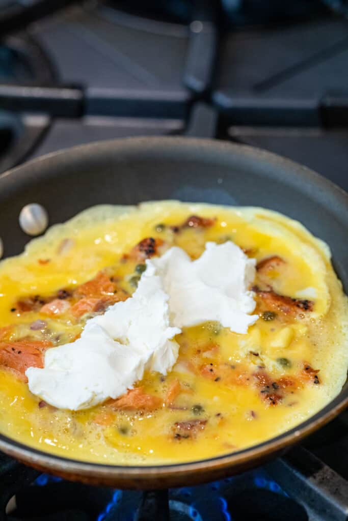 Adding cream cheese to the omelette.
