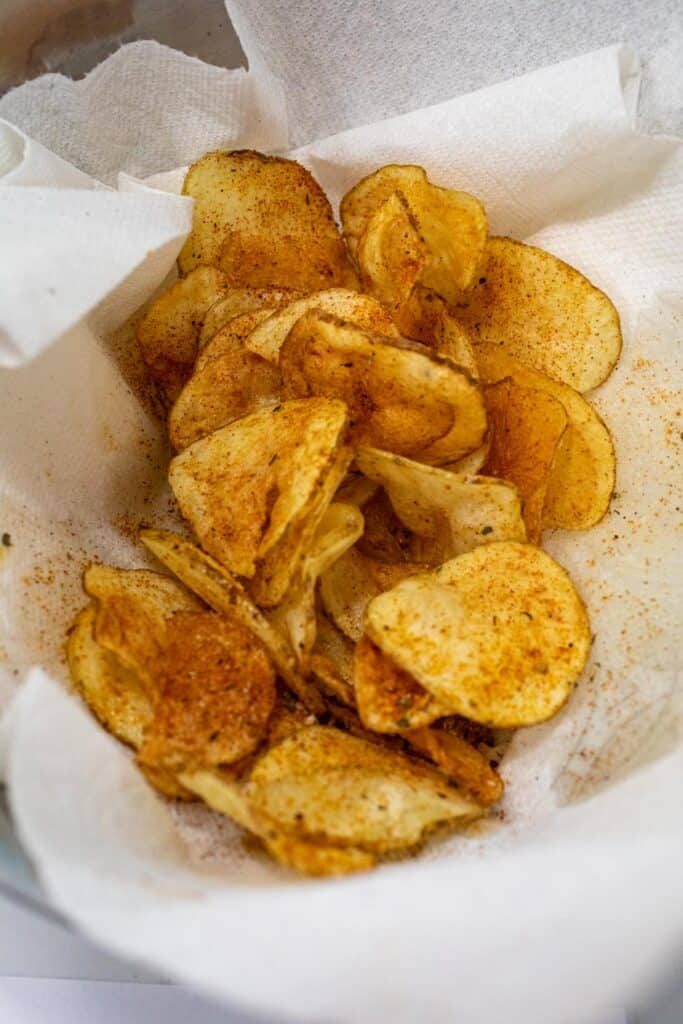 Draining and seasoning the chips after frying.