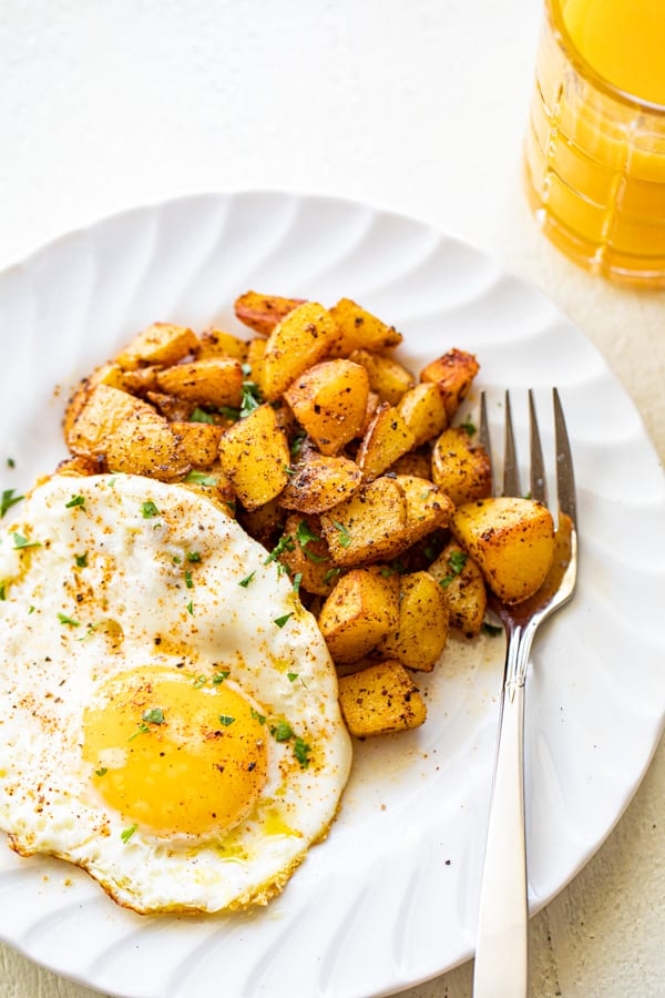 Home fries on a plate with a side of sunny side up eggs.