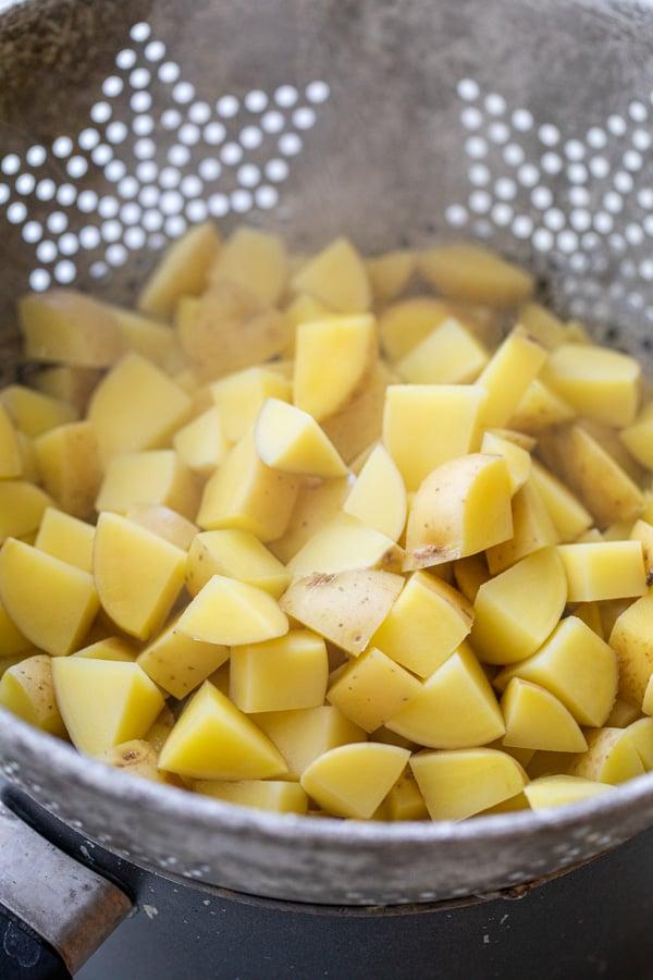 Par boiling the potatoes after cubing them.