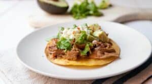 Traditional pork tinga simmered with peppers and spices and served on tostadas with classic toppings. Via Macheesmo.