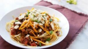 A classic cincinnati chili version with beef and bean chili served over plain spaghetti with lots of great toppings like shredded cheese, scallions, and crackers. Chili never tasted so good!