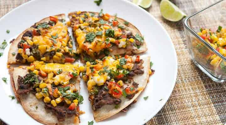 Black Bean and Corn Tortilla Tart: A half quesadilla and half pizza meal that's easy to make but different from your standard Tex-Mex recipe. Layers of black beans mashed with spices and a fresh corn salsa with two kinds of cheese and baked until crispy.