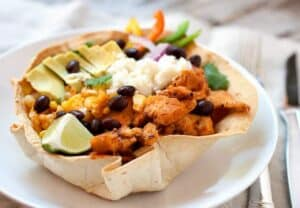 Chipotle Chicken Taco Bowls! I don't mean Chipotle like the restaurant, these chicken taco bowls are so much better! Spicy chipotle chicken layered with corn, black beans, cilantro rice, and other great taco toppings in an edible taco bowl! | macheesmo.com