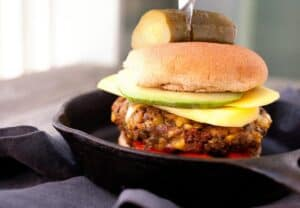 Spicy Lentil Burgers! Beautiful green lentils mashed with lots of spice, shaped into burgers, and cooked until crispy on the edges. Served with fresh mango, avocado, and roasted red peppers!