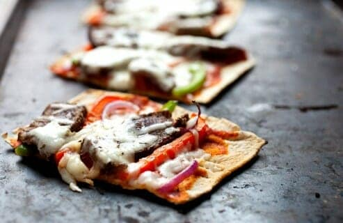 Cheesesteak Flatbread: Flatbreads topped with sliced sirloin steak, peppers, onions, and provolone cheese. Great as a meal or a hearty appetizer. Super easy to make thanks to Flatout Flatbread pizza crust! #sponsored | macheesmo.com