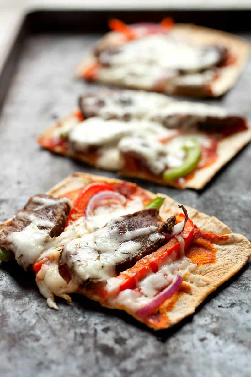 Cheesesteak Flatbread: Flatbreads topped with sliced sirloin steak, peppers, onions, and provolone cheese. Great as a meal or a hearty appetizer. Super easy to make thanks to Flatout Flatbread pizza crust! #sponsored   macheesmo.com