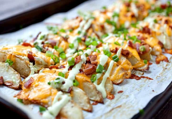 Loaded Potato Wedges - Appetizer? Side dish? Main meal? These completely loaded baked potato wedges can be anything you want. Cheddar, chives, and an avocado sour cream sauce. Potato perfection! | macheesmo.com