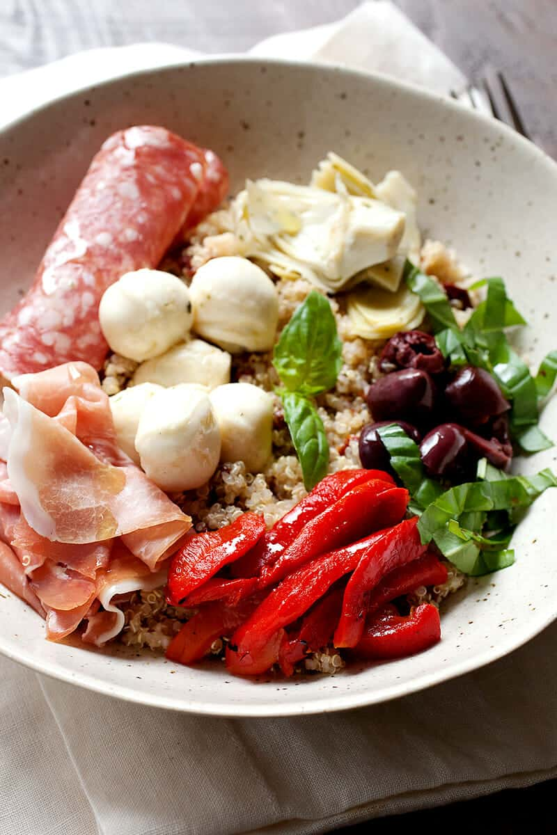 Antipasto Quinoa Bowls: Barely a recipe, this cross between a quinoa bowl and a traditional Italian Antipasto course has all of my favorite things. Of course, the nice thing about it is you can make it your own! Be sure to check out the recipe for my quinoa flavor BOOST trick! | macheesmo.com