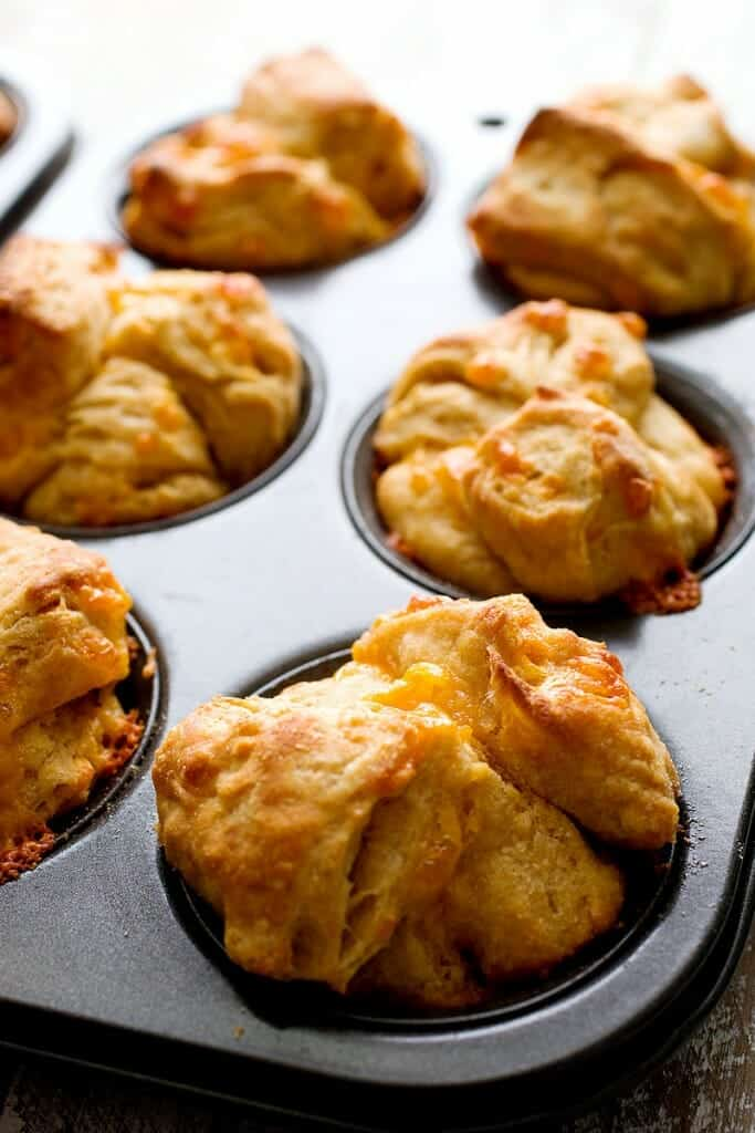 Pull Apart Cheddar Buttermilk Biscuits: Made from scratch biscuits with loads of sharp cheddar folded in. Chopped up (monkey bread style) and baked in muffin tins so they pull apart easily. Great for kiddos or adults! | macheesmo.com
