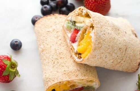 Rainbow Breakfast Wraps: These quick wraps are so quick to make an a perfect way to start the day. Packed with granola, Greek yogurt, and colorful fruits and stuffed inside a flatbread. #sponsored | macheesmo.com