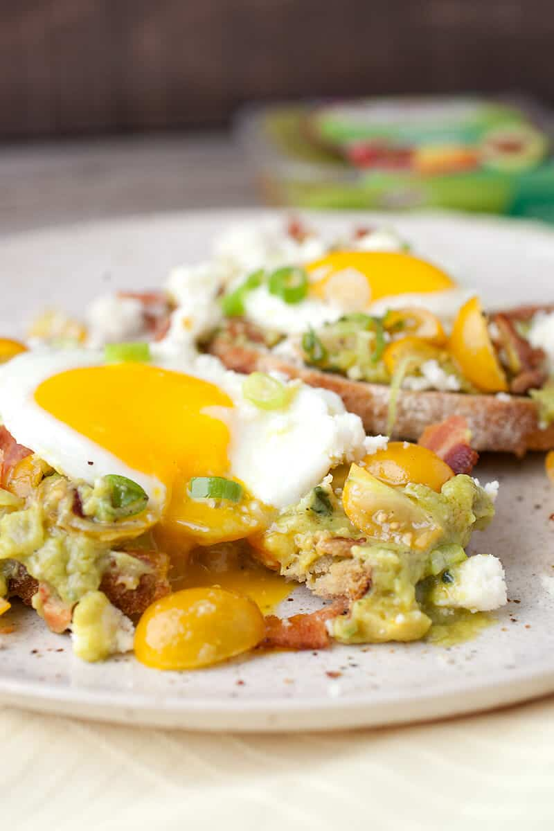 Loaded Guacamole Toasts: A twist on your simple avocado toast with veggie-packed guacamole, bacon, crumbled cheese, a fresh tomato salad, and a sunny-side up egg. Start your day off right! | macheesmo.com