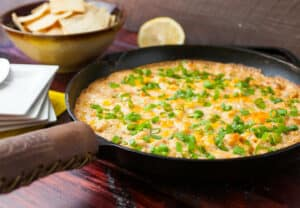 Easy Baked Shrimp Dip: This baked shrimp dip is the perfect warm appetizer. Fresh shrimp baked together with peppers, spices, and some cheese makes for and easy and irresistible appetizer! I baked and served my version right in my cast iron skillet! | macheesmo.com