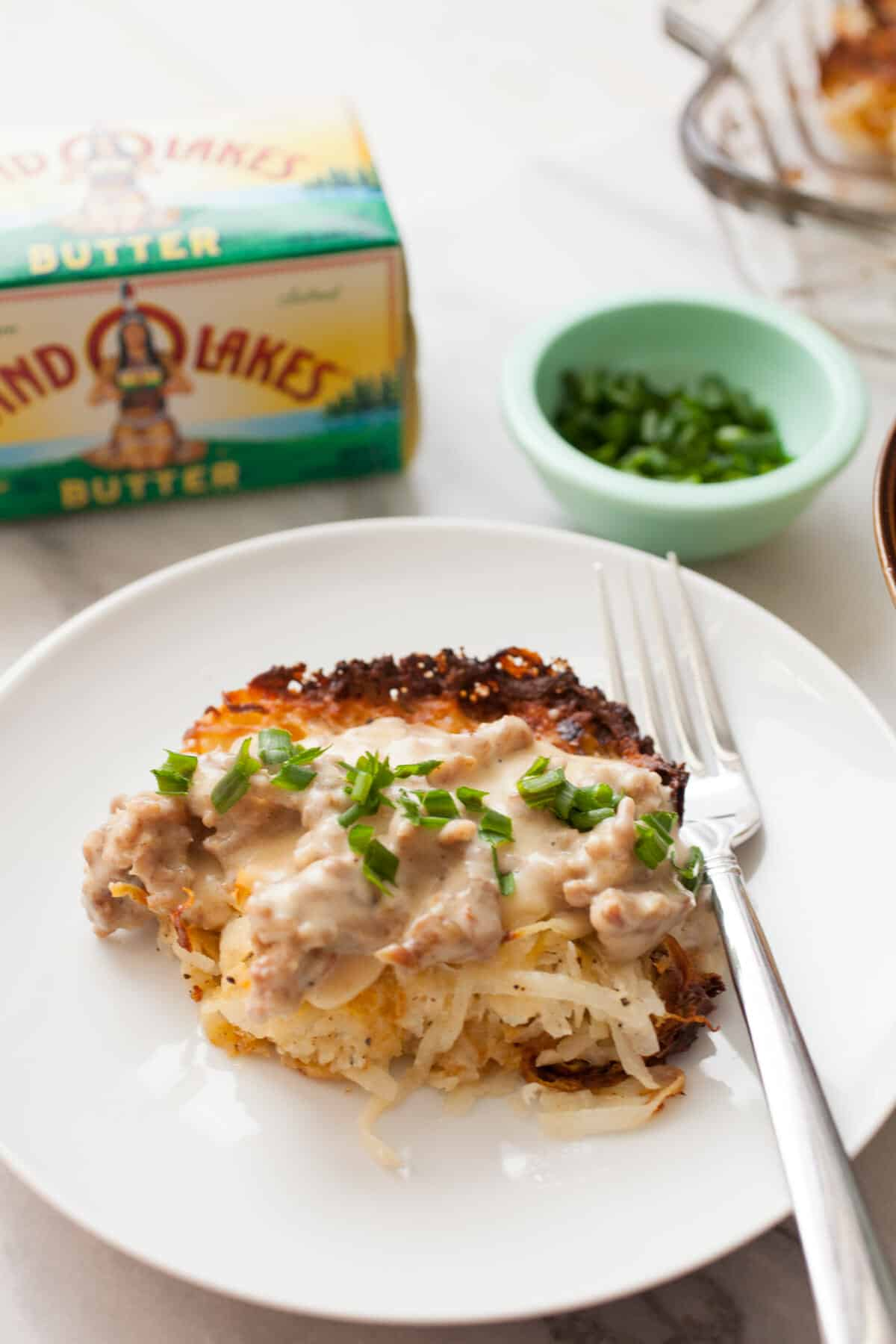 Potato Casserole with Sausage Gravy: This is slow comfort food at its best. Homemade simple potato casserole with fresh potatoes topped with a hearty sausage gravy. Comfort food on a plate! | macheesmo.com