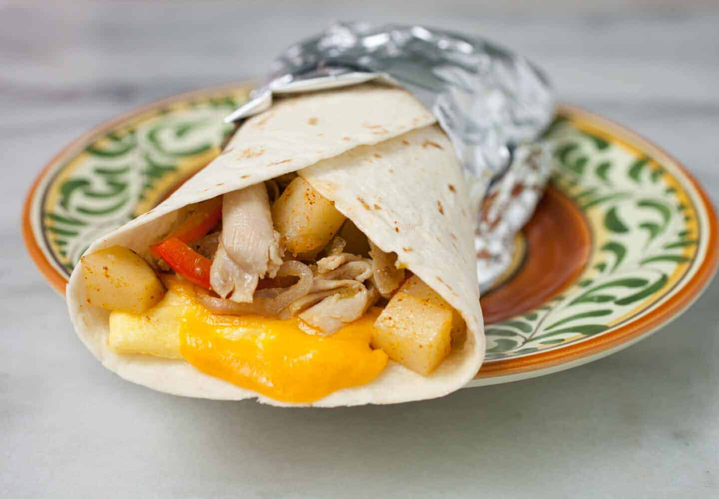 Rotisserie Chicken Breakfast Burritos: These super-cheesy and delicious breakfast burritos use one of my favorite meal shorted (rotisserie chicken) so they are ready to go in just a few minutes! | macheesmo.com