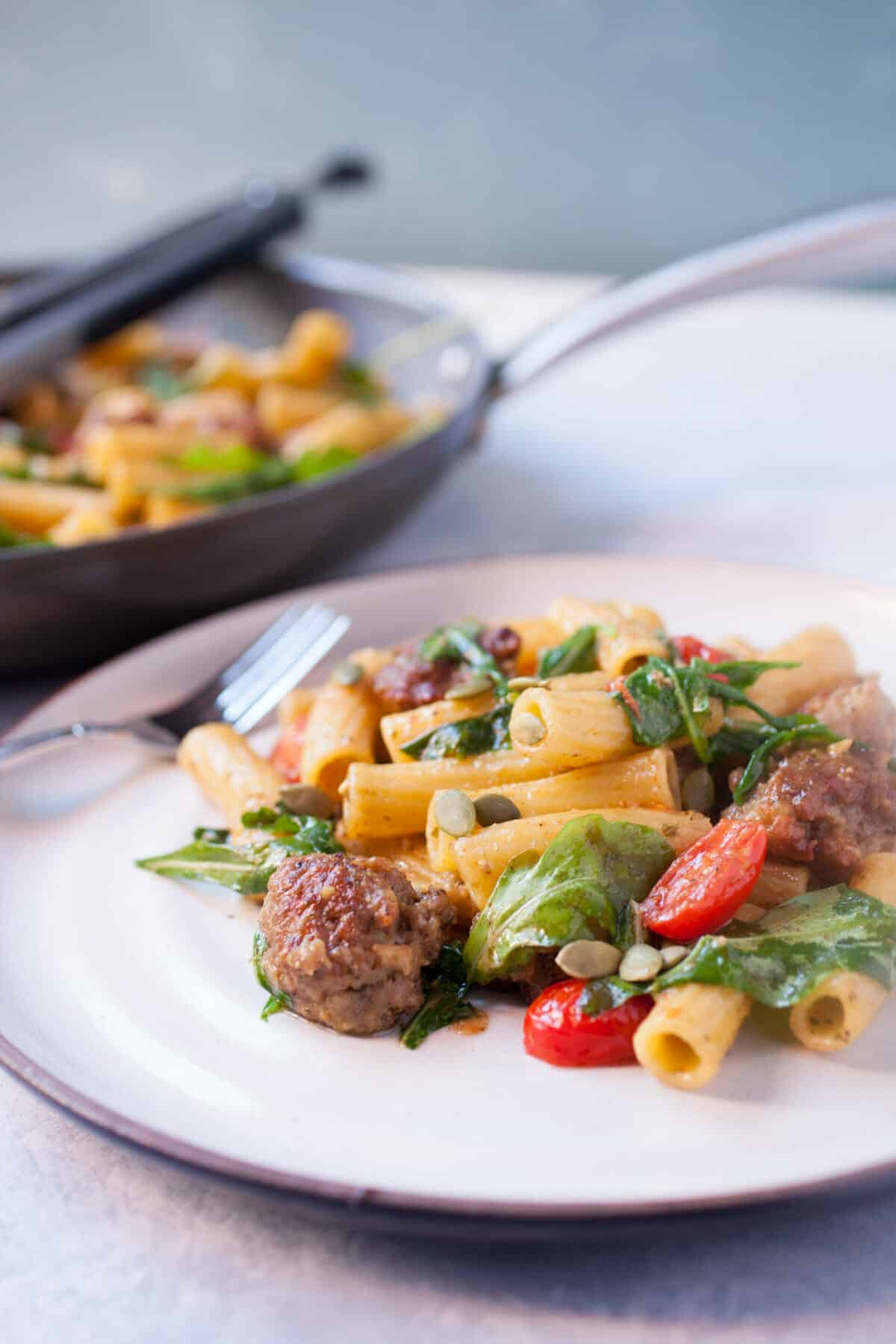 Easy Pesto Pasta with Sausage: This pasta dish is perfect comfort food. Simple flavors with sweet Italian sausage, arugula, and grape tomatoes, tossed with pasta and pesto. One of my new favorites! | macheesmo.com