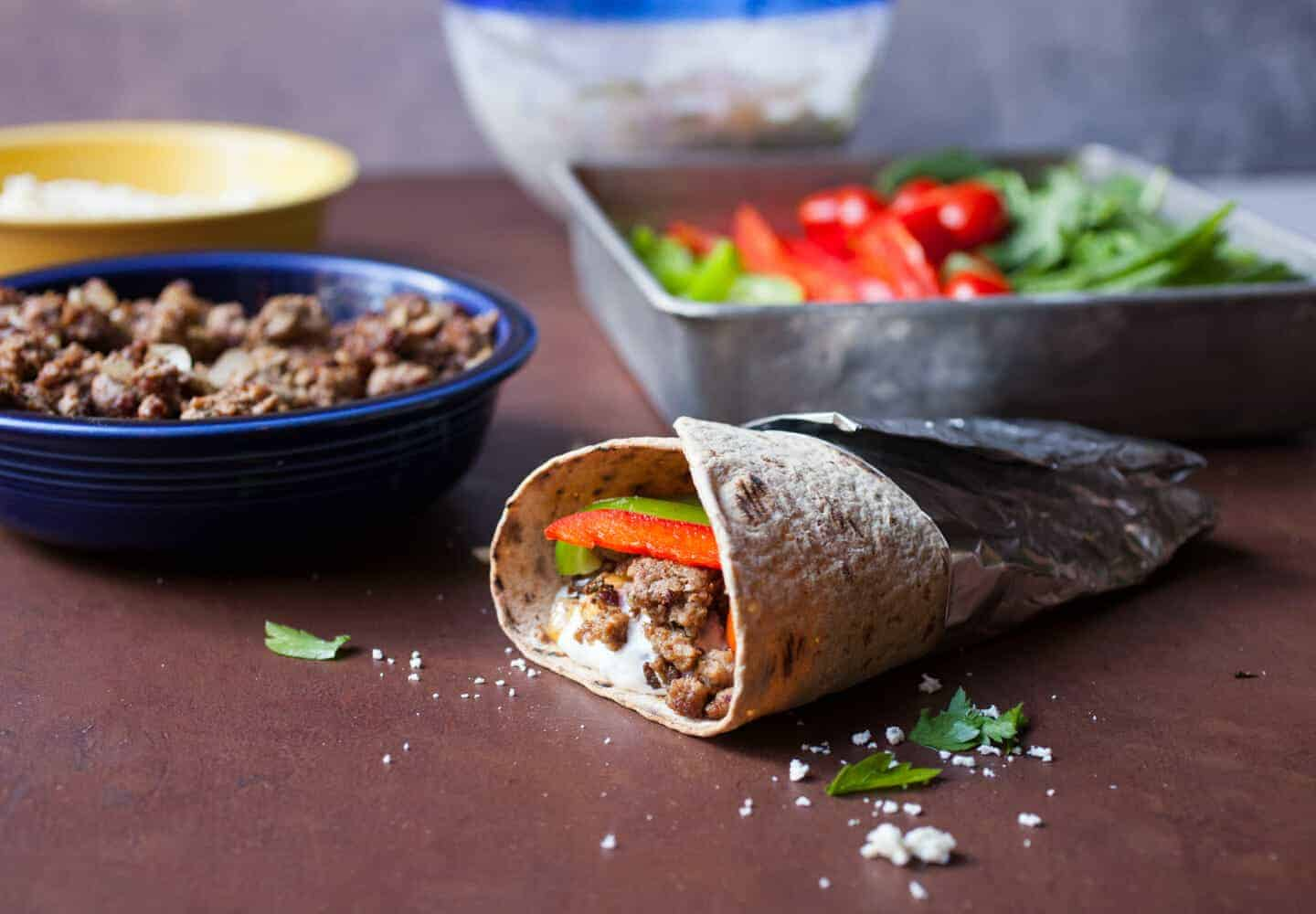 Lamb Gyro Flatbread Wraps: Savory ground lamb served with a labneh tzatziki sauce and fresh veggies in a Flatbread wrap. One of my new favorite wraps, for sure! | Macheesmo.com