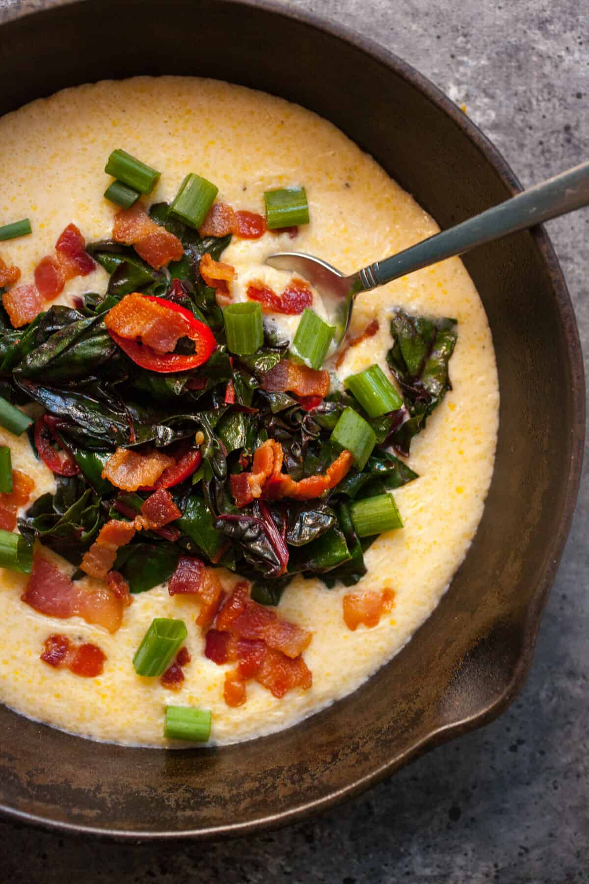Chard and Bacon Polenta Bowls: These are perfect bowls for a cool winter night. Warming, delicious polenta topped with sauteed chard, bacon bits, and spicy peppers. YUM. | macheesmo.com