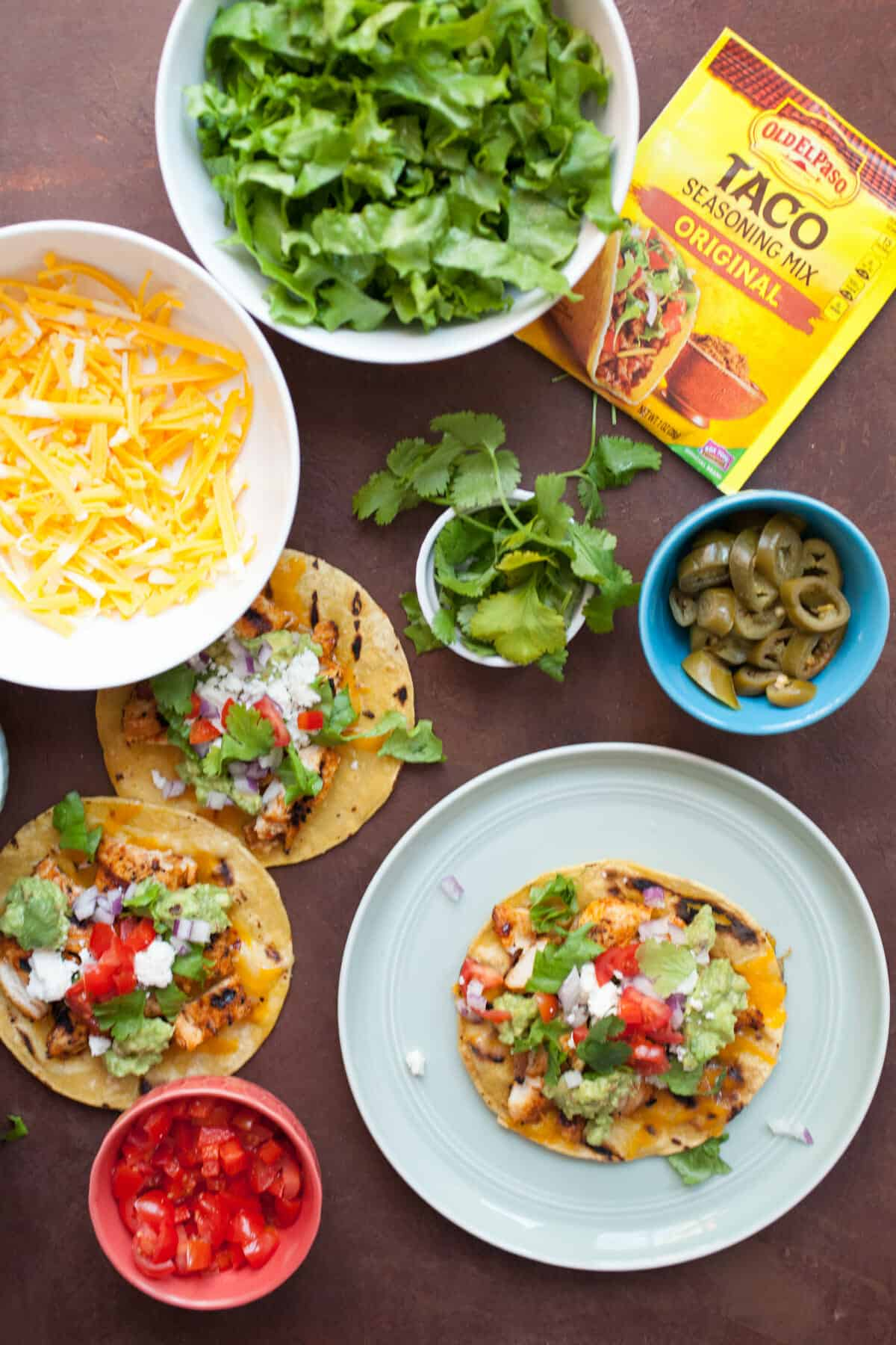 Grilled Chicken Tostadas: Say hello to grilling season the right way with these easy grilled chicken tostadas! Topped with spicy fajita chicken, cheese, and toppings and made entirely on the grilll! | macheesmo.com
