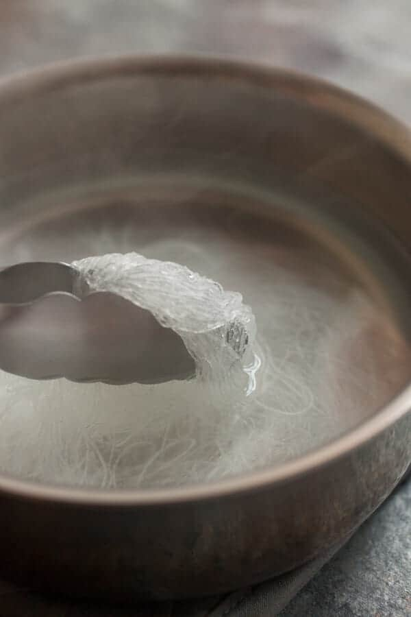 Boiling glass noodles in water.