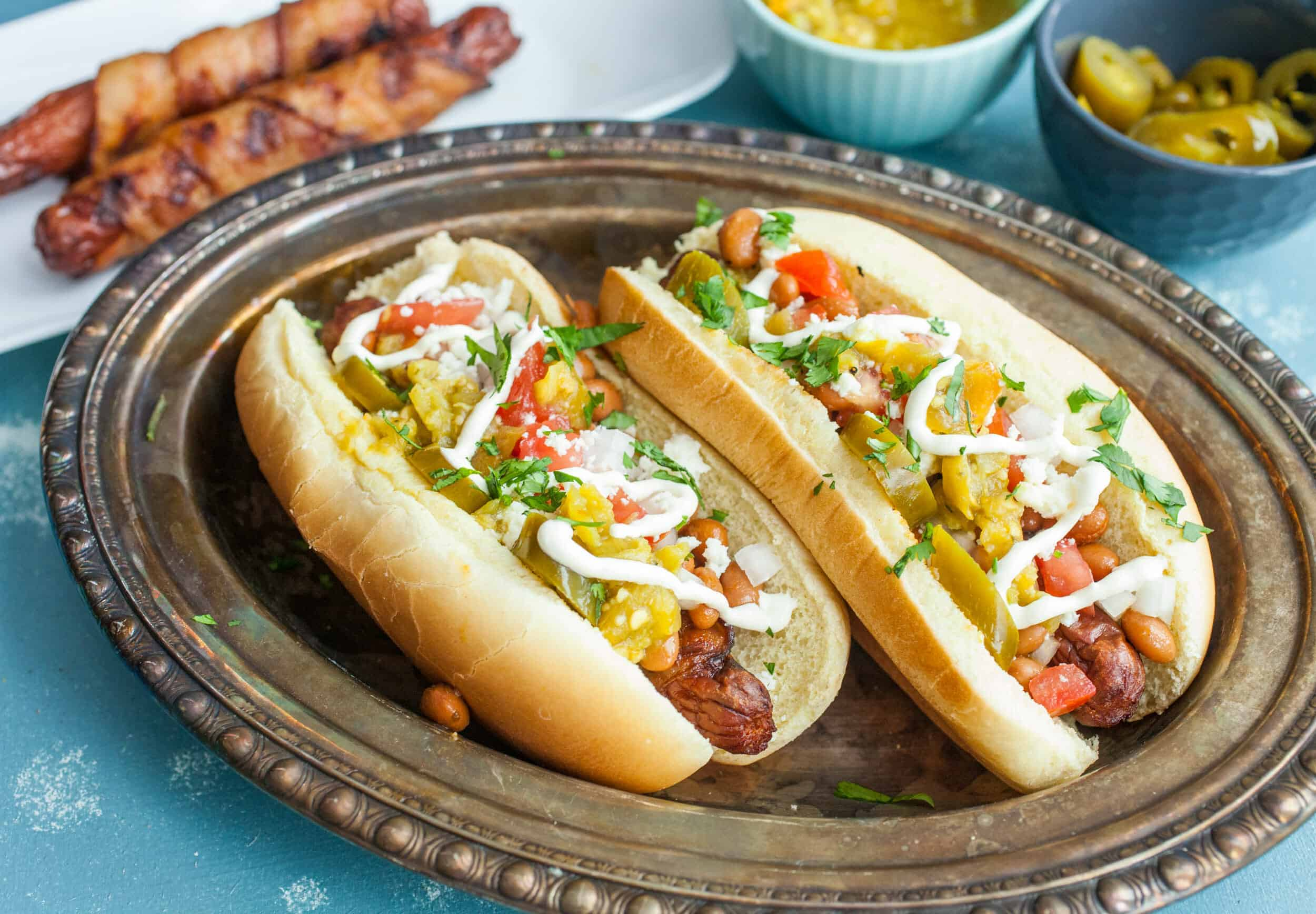 Sonoran Hot Dogs: Bacon wrapped grilled hot dogs topped with ALL the toppings you could ever want. These are the perfect jazzed-up hot dog for a backyard party! Inspired by the popular Tucson version. | macheesmo.com
