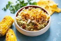 Street Corn Guacamole: Homemade guacamole mixed with a few simple, but perfect add-ins that mimic Mexican street corn (elote)! Roasted corn, cotija cheese, chili powder, cilantro, and a few other goodies. Perfect for a party! | macheesmo.com