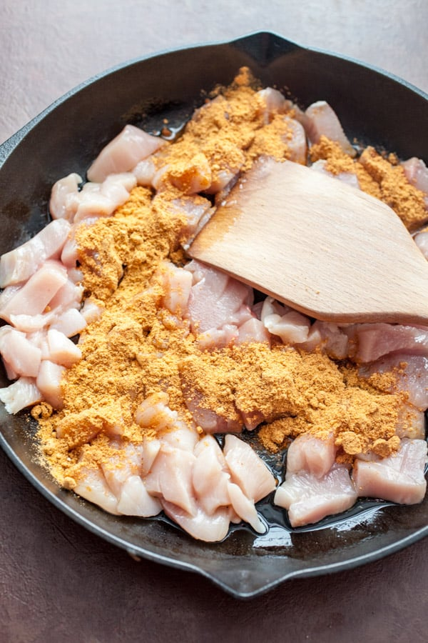 Cooking chicken and spices in the skillet for taco skillet.