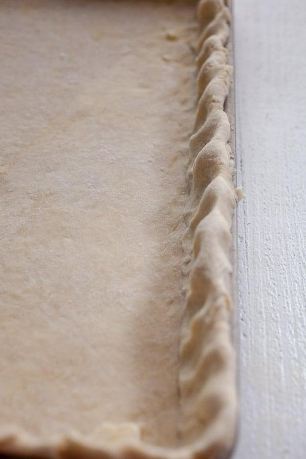 Quiche dough shaped in the sheet pan.
