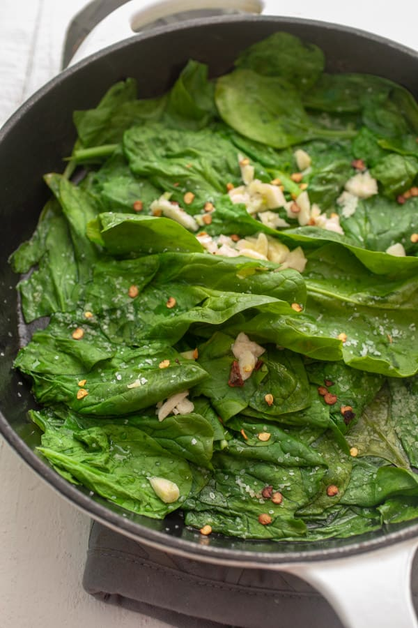 Cooking spinach for quiche filling.