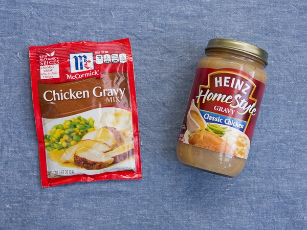 A package of powdered gravy mix next to a jar of premade gravy on a blue background