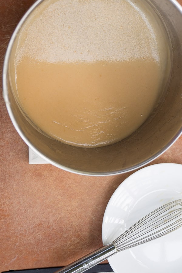 thickened gravy in saucepan next to a whisk and plate