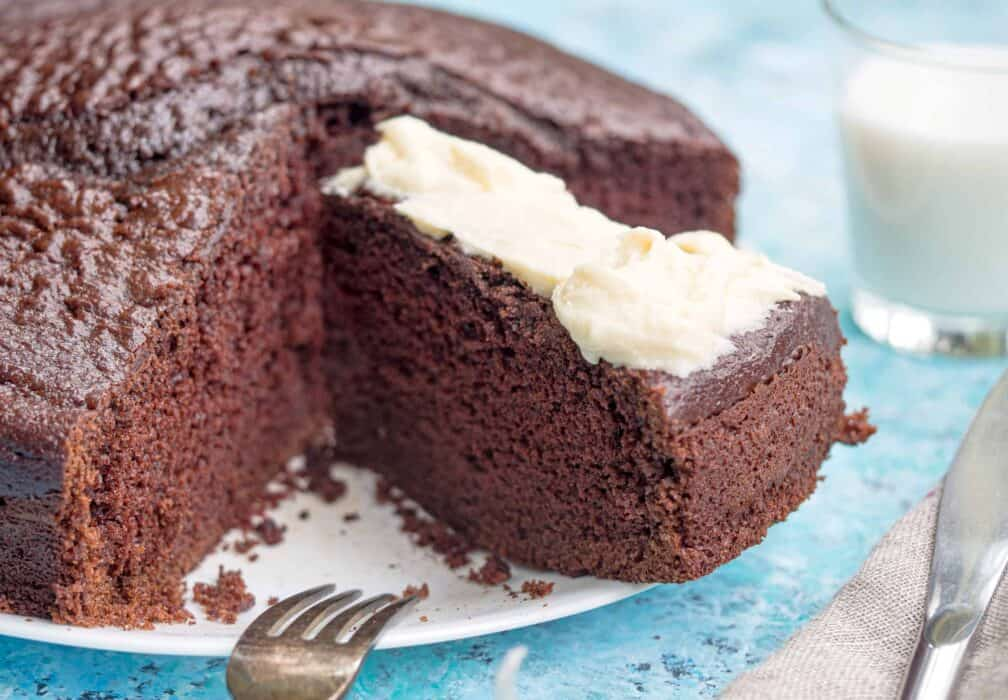 homemade chocolate cake on a white plate with cream cheese frosting