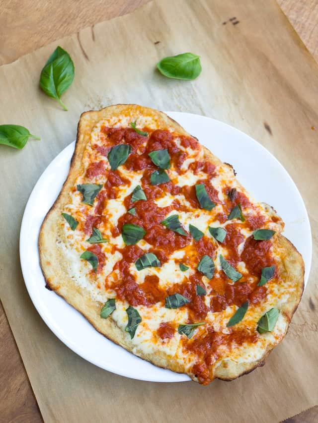 A homemade pizza Margherita on a white plate next to basil leaves