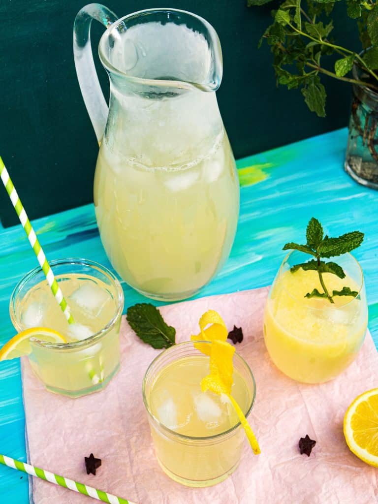 3 glasses and a pitcher of lemonade with mint garnish