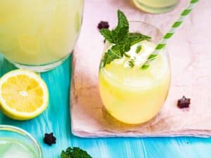A glass of lemonade with a mint garnish and a green-white striped straw