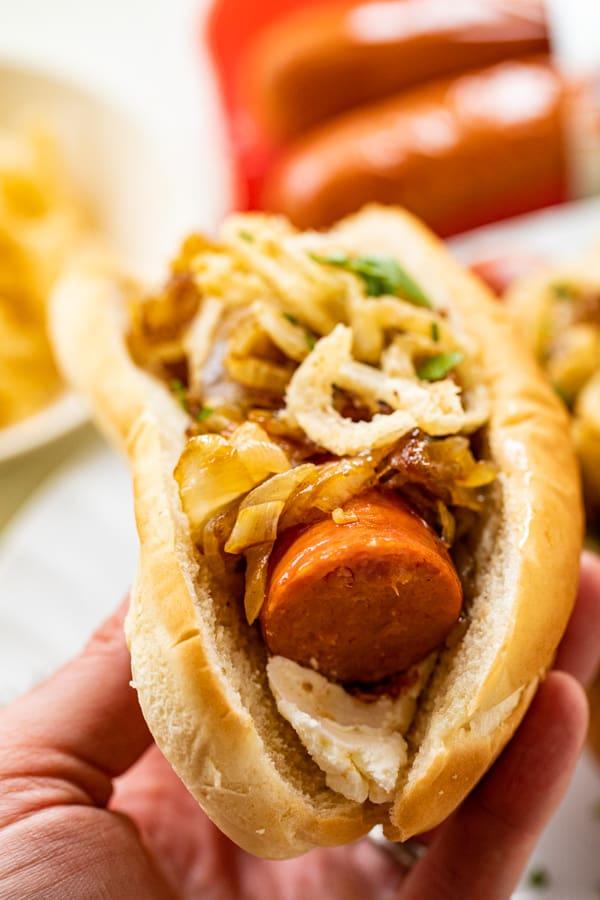 Bite of a caramelized onion sausage dog.