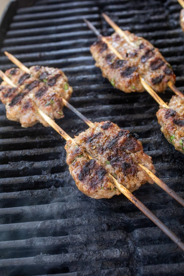 Pork meatballs on the grill cooking.