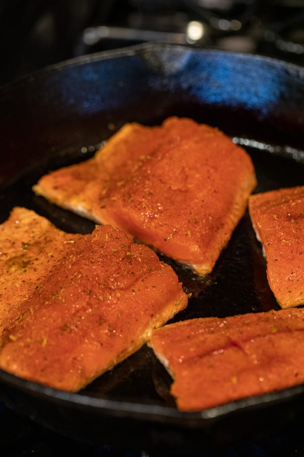 Starting to sear the salmon with blackening seasoning in cast iron.