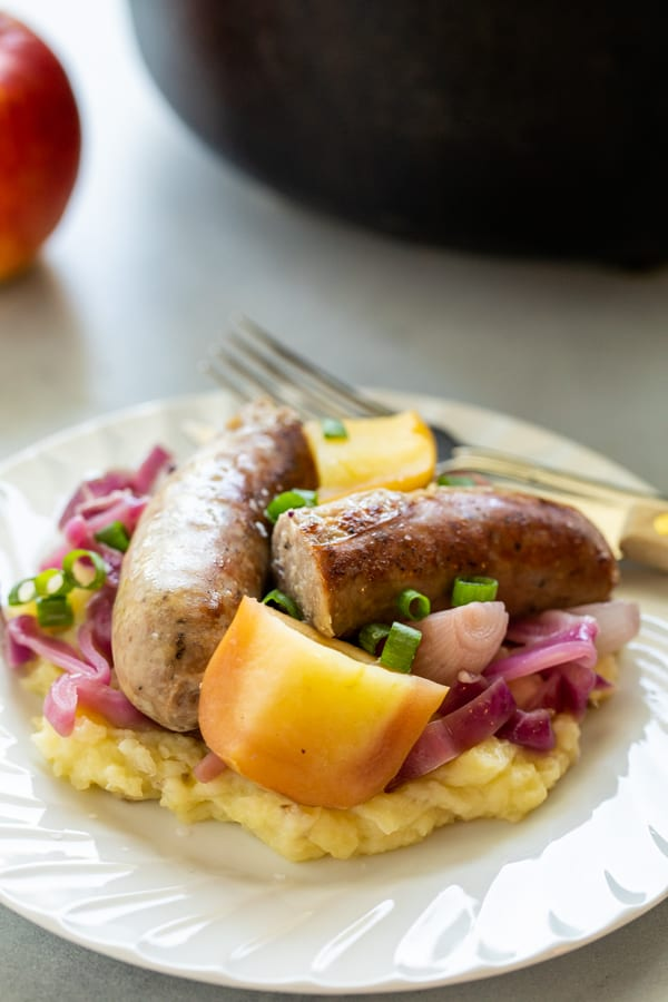 Braised apples and sausage on plates