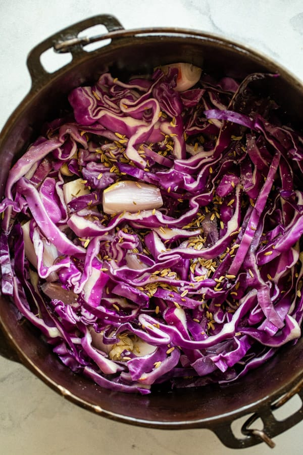 Adding cabbage to skillet for braised apples.