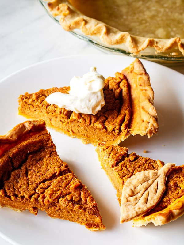 3 slices of pie on a white plate next to a pie crust