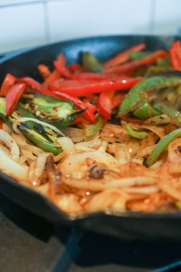 Cooking fajita veggies in a skillet.