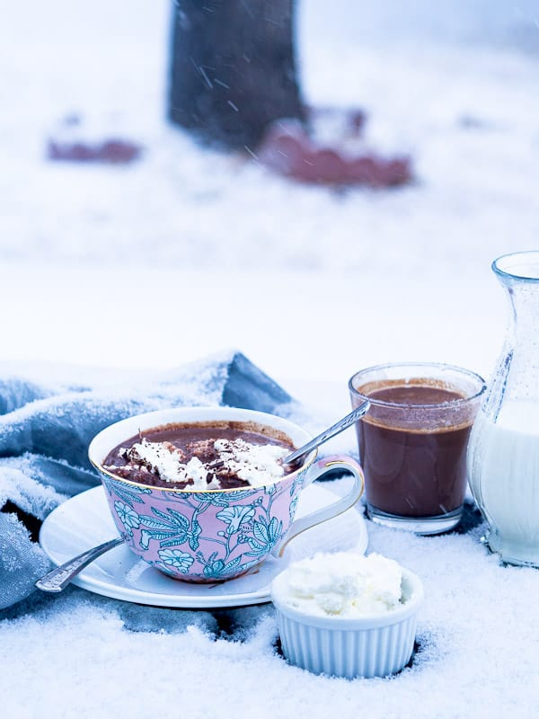 2 cups of hot chocolate next to containers of whipped cream and milk in front of falling snow