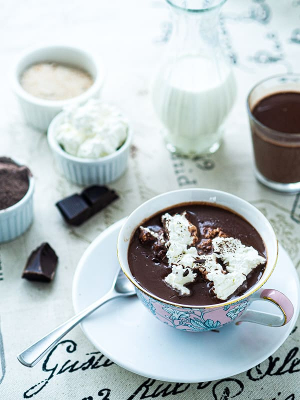 2 cups of hot chocolate next to whipped cream, sugar, milk, and cocoa powder.